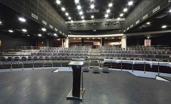 Document stand on stage and rows of chairs with handrails in large hall for business meetings.